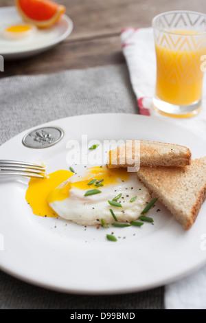 fried egg and toast with orange juice - Stock Photo