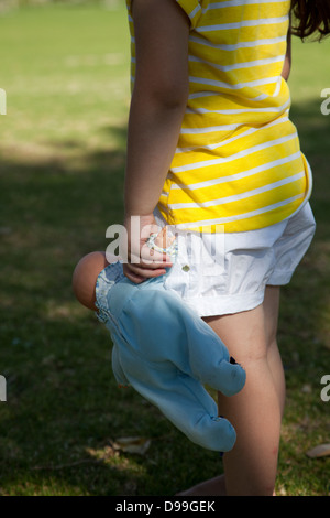Girl Holding Baby Doll - Stock Photo