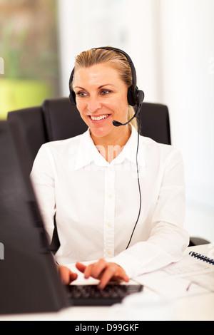 happy senior businesswoman with headphones in front of computer - Stock Photo