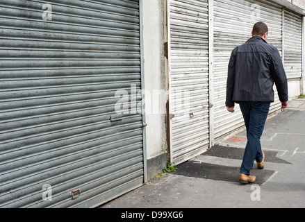A man walking past a row of closed down shops in Stretford, Manchester, England, UK - Stock Photo