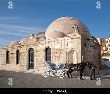 Horse with carriage and driver beside the Turkish Yiali Tzami  Mosque at Venetian Harbour in old town Chania - Stock Photo