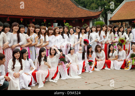 Young female college graduates pose for a portrait at the Temple of Literature in Hanoi, Vietnam, Southeast Asia - Stock Photo