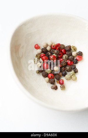 White bowl with variety of peppercorns - Stock Photo