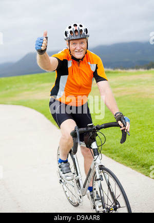 happy senior male bicyclist giving thumb up on bicycle - Stock Photo