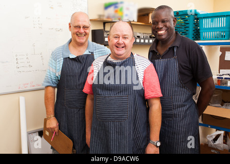 happy senior small business owner and two employees in workshop - Stock Photo