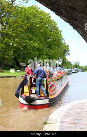 Family sailing a narrowboat on the Shropshire Union canal near Nantwich, England - Stock Photo