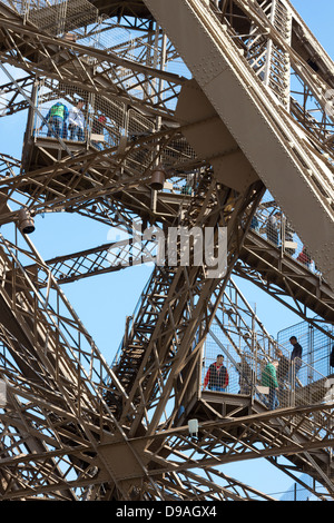 Tourists walking down steps through complex lattice iron girders to descend from first level of Eiffel Tower in - Stock Photo