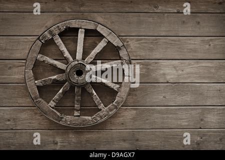 An old wooden wagon wheel on the wall of a barn - Stock Photo