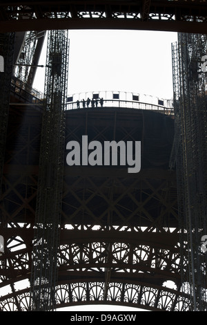 Silhouette of people looking out from first level platform of Eiffel Tower surrounded by decorative ironwork - Stock Photo
