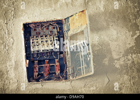 Old bad rusty switch box on the weathered wall - Stock Photo