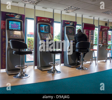 Roulette machines (FOBT fixed odds betting terminal) in Ladbrokes Bookmakers, England, UK - Stock Photo