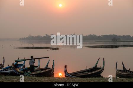 Sunrise over fisherman's boat by Ubein bridge Mandalay Burma - Stock Photo