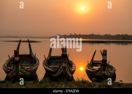 Sunrise over fisherman's boat by Ubein bridge Mandalay Burma Myanmar - Stock Photo