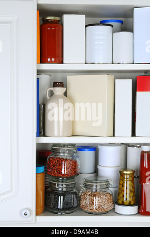 Closeup of a well stocked pantry. One door of the cabinet is open revealing canned goods, condiments, package foodstuffs - Stock Photo
