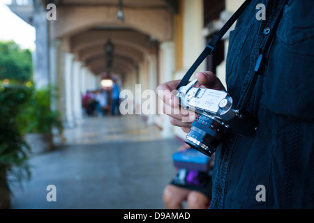 A photographer photographs street subjects with a traditional film camera, a Leica M3 in Granada, Nicaragua. - Stock Photo
