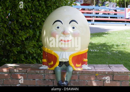 A Statue of Humpty Dumpty sat on a Red Brick Wall - Stock Photo