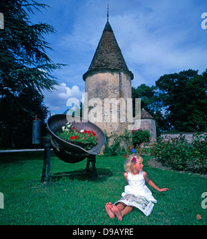 Le château de la Berchère. A pretty, five year old blonde girl, in a white dress, sitting alone in the garden of - Stock Photo