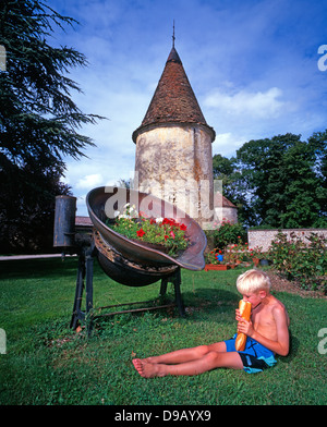 Le château de la Berchère. A seven old boy eating a baguette, sitting alone in the garden of a chateau hotel in - Stock Photo