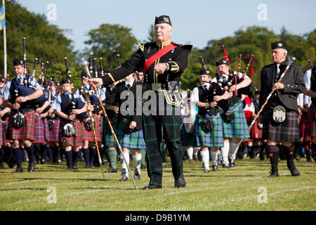 Aberdeen, UK. 16th June, 2013.  Massed pipe bands marching on to the field at the Highland Games in Hazlehead Park, - Stock Photo