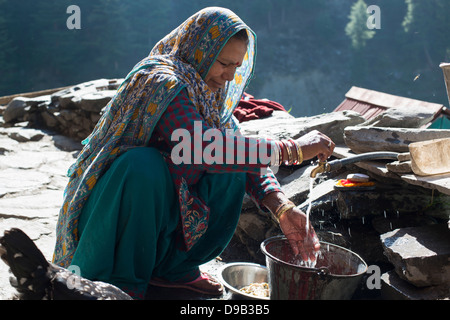 A Gaddi tribal matriarch washes the family's dishes at the Himalayan village of Kugti in Himachal Pradesh, India - Stock Photo