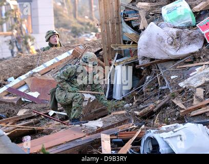 Japan Ground Self-Defense Force troopers shift through the debris as search-and-rescue operations are launched near Sendai Airport, Miyagi prefecture, on Monday, March 14, 2011. The airport, located along the Pacific coast, was flooded by a 10-meter tsuna Stock Photo