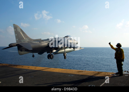 A US Marine Corps AV-8B Harrier fighter aircraft from takes off from the flight deck of the amphibious assault ship - Stock Photo