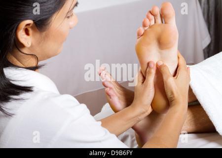 Asian woman giving professional foot massage - Stock Photo