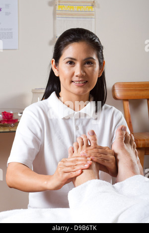 Asian masseuse giving professional foot massage - Stock Photo