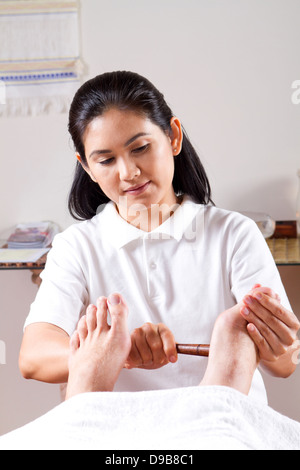 asian masseuse giving foot massage in spa center - Stock Photo