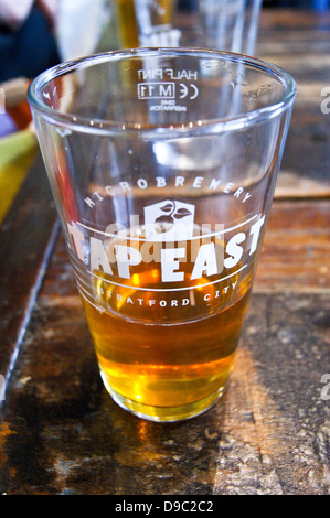 A pint of pale ale in a printed glass at Tap East bar, Westfield, Stratford, London, England. Cropped landscape - Stock Photo