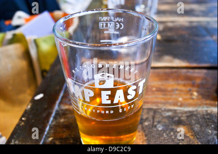 A pint of pale ale in a printed glass at Tap East bar, Westfield, Stratford, London, England pub table drinks glasses - Stock Photo