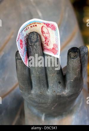 Vietnam Chua Bai Dinh Pagoda: Close up of Buddhist Philosopher's hand with money between fingers. - Stock Photo