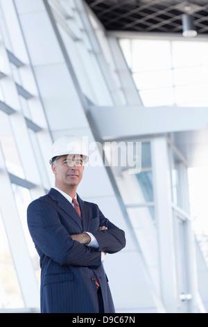 Portrait of businessman wearing hard hat - Stock Photo