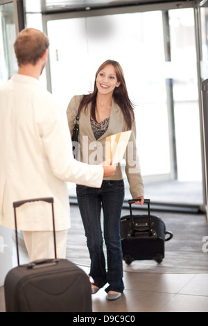 Woman with suitcase and man with airline tickets - Stock Photo