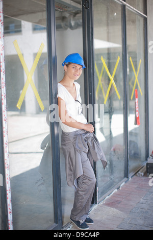 Portrait of female construction worker on construction site - Stock Photo