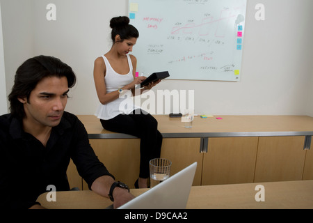 Young man using laptop with woman in background - Stock Photo