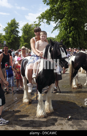 A gypsy mother and son ride their horse bareback after washing it in the River Eden at Appleby Horse Fair, in Cumbria, - Stock Photo