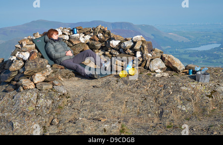 A hiker wild camping on the summit of Robinson in the Lake District - Stock Photo
