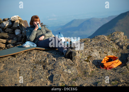 A female hiker enjoying an early morning cup of tea after camping on the summit of Robinson in the Lake District - Stock Photo