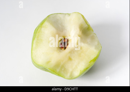 A half eaten green apple showing the core and seeds - Stock Photo