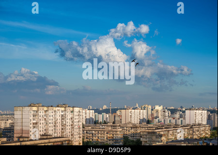 Sunset with cumulonimbus clouds on blue sky in cityscape. Two swallows flying over cloud. Kiev, Ukraine - Stock Photo