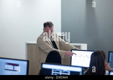 Students using computers in lecture - Stock Photo