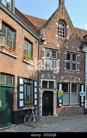A house for sale in a side street in Bruges, Belgium, Europe. Familar bicycles in view. - Stock Photo