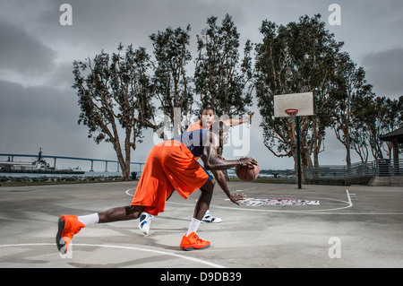 Young men playing basketball on court - Stock Photo