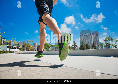 Young man jogging in city, low section - Stock Photo