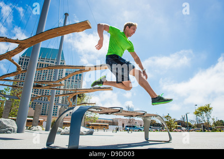 Young man leaping over park bench in city - Stock Photo