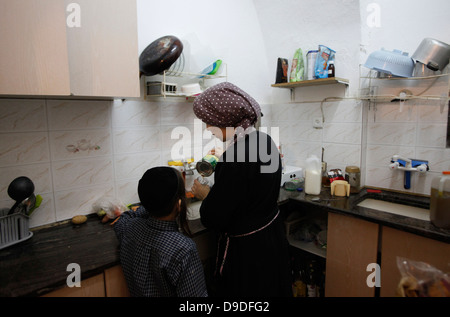 An Orthodox religious Jewish woman with her child in her kitchen in Mea Shearim neighborhood West Jerusalem Israel - Stock Photo