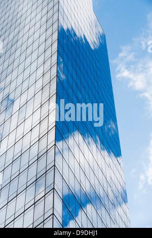 Blue cloudy sky reflected in windows of modern skyscraper - Stock Photo