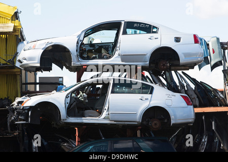 Cars stacked in scrap yard - Stock Photo