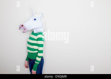 Girl wearing unicorn head - Stock Photo